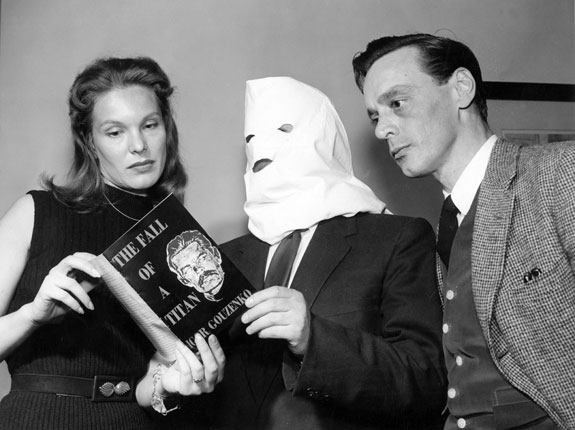 "Two people look over the shoulders of a third person to examine a book titled ""The Fall of a Titan"" by Igor Gouzenko. The author stands in the middle of the two other people, holding the book. His face is obscured by a white bag with small holes cut for his eyes and mouth."